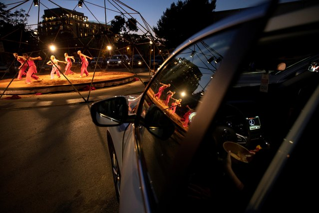 """People sit inside their cars and watch an open-air performance of """"Birth of the Phoenix"""" by Vertigo Dance Company at the parking lot of Jerusalem's Old Station amid the coronavirus crisis, in Jerusalem on August 4, 2020. (Photo by Ronen Zvulun/Reuters)"""
