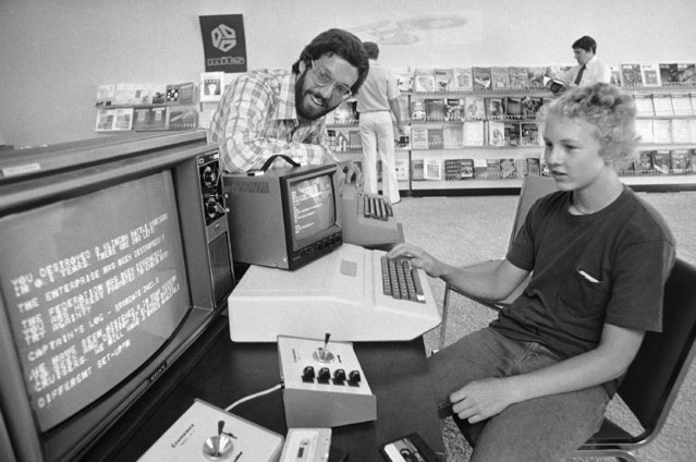 """Richard Conner, 15, plays a game of """"Star Trek"""" on a small, relatively cheap """"home"""" computer at the Computer Store which is owned by Dick Heiser, left, in Los Angeles on September 22, 1977. The so-called microcomputers are used for everything from playing games to doing your income tax yourself. (Photo by George Brich/AP Photo)"""