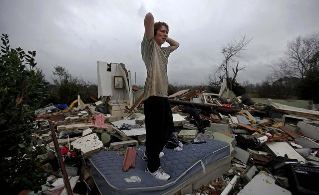 Will Carter, 15, surveys the damage to his house upon arriving home from school after a tornado tore through Adairsville, Georgia. (Photo by David Goldman/Associated Press)