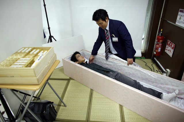 Noriaki Iwashima lies in a coffin to test it during an end-of-life seminar held by Japan's largest retailer Aeon Co in Tokyo October 24, 2014. (Photo by Toru Hanai/Reuters)