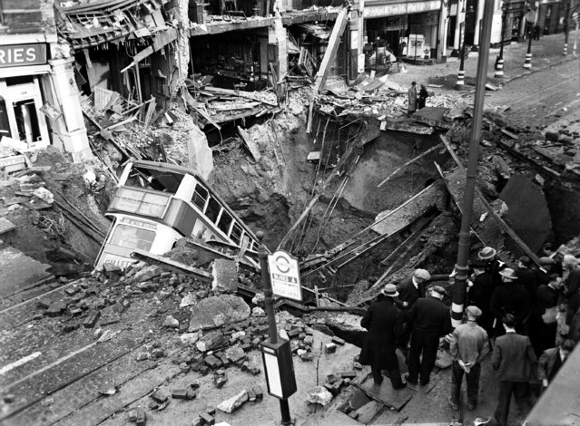 Following a large air raid by German bombers, local people, coming out of their air raid shelters found a bus standing on end in a large crater, in Balham, London, October 15, 1940. (Photo by AP Photo)
