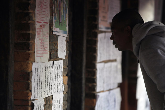 A Nepalese man checks his name on the voters list during the legislative elections in Bhaktapur, Nepal, Thursday, December 7, 2017. (Photo by Niranjan Shrestha/AP Photo)