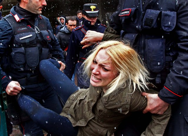 Police remove a woman who was protesting in Milan where former Italian Premier Silvio Berlusconi was voting in a watershed parliamentary election that could shape the future of one of Europe's biggest economies, on February 24, 2013. (Photo by Spada/Lapresse)