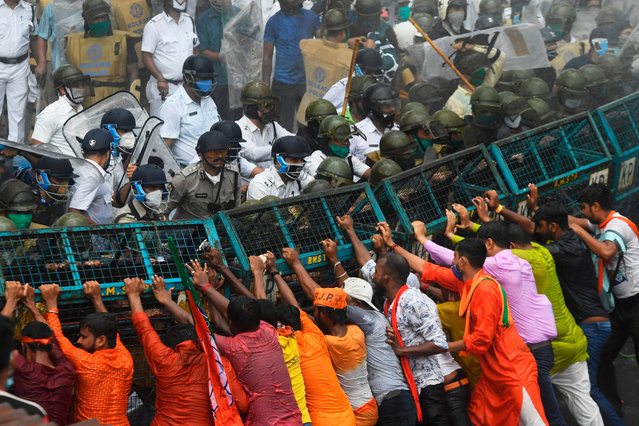 """Activists of the Bhartiya Janata Party (BJP) try to breakthrough a police barricade during a protest march towards West Bengal Chief Minister Mamata Banerjee's office to protest against the """"worsening"""" law and order situation in the state, in Kolkata on October 8, 2020. (Photo by Dibyangshu Sarkar/AFP Photo)"""