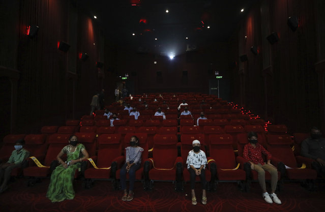 People watch an Indian Bollywood movie as cinemas reopen with a special screening for COVID- 19 warriors and their families at the PVR movie theater in New Delhi, India, Thursday, October 15, 2020. Seven months after screens went dark, cinemas reopened Thursday in much of India with mostly old titles on the marquee — a sign of the country's efforts to return to normal as the pace of coronavirus infections slows but also of the roadblocks that remain. (Photo by Manish Swarup/AP Photo)