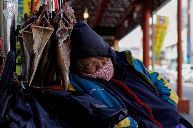 A vendor sleeps in a local market in Gangneung, South Korea, February 23, 2018. (Photo by Mike Segar/Reuters)