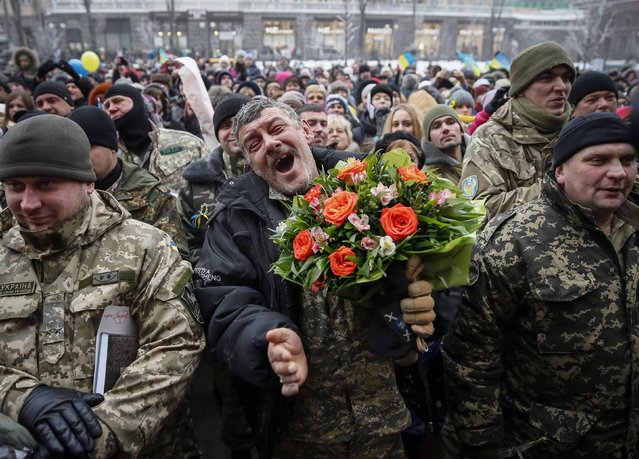 "Servicemen of ""Kiev 12"" military defence battalion react as they take part in a welcoming ceremony in central Ukrainian capital Kiev December 6, 2014. Servicemen of the battalion returned to Kiev after taking part in fighting in eastern Ukraine. (Photo by Gleb Garanich/Reuters)"
