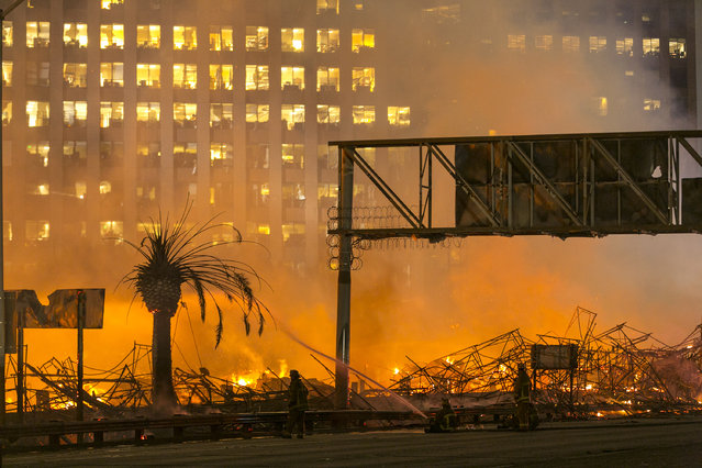 Los Angeles County firefighters battle a fire at an apartment building under construction next to the Harbor CA-110 Freeway in Los Angeles, early Monday, December 8, 2014. The building was not occupied, the Los Angeles Fire Department reported. (Photo by Damian Dovarganes/AP Photo)