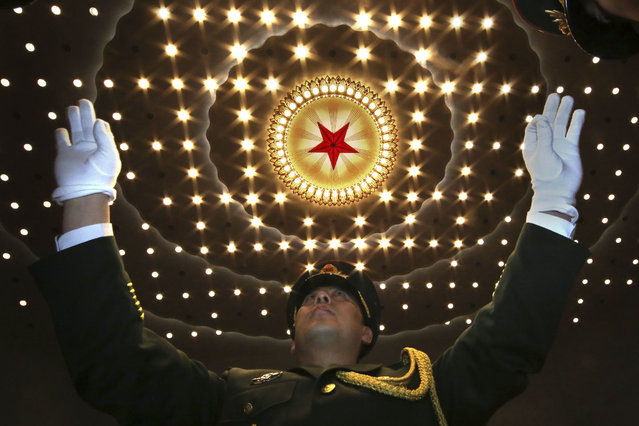 A Chinese military band conductor leads the band at the end of the opening session of the annual National People's Congress in Beijing's Great Hall of the People, Monday, March 5, 2018. China's government pledged Monday to deliver robust growth, pursue advanced technology and boost military spending while urging the public to embrace President Xi Jinping's rule as its ceremonial legislature prepared for changes to allow him to stay in power indefinitely. (Photo by Ng Han Guan/AP Photo)