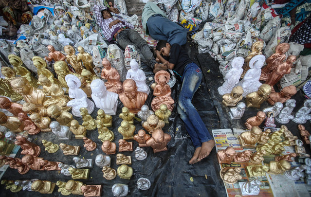 Indian Dalits take naps near statues of B.R. Ambedkar, displayed for sale on his 58th death anniversary in Mumbai, India, December 6, 2014. Ambedkar was a low-caste Hindu leader who fought against discrimination due to caste. (Photo by Divyakant Solanki/EPA)