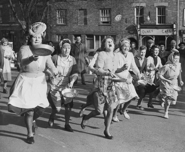 British housewives toss pancakes in skillets as they run through the streets of Olney, England, in the community's annual race which follows a 500-year-old tradition, February 6, 1951. Mrs. Isabel Dix, 22, extreme right, won the race covering the 415 yards from the Parish pump to the door of Sts. Peter and Paul church in one minute, 12.1 seconds. (Photo by AP Photo)