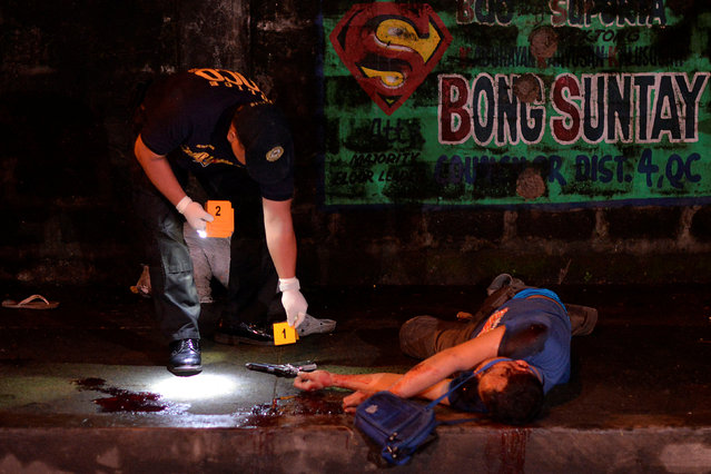 """A police investigator places a label on a revolver found near the body of one of two men, who police said were killed after a drug """"Shabu"""" (Methamphetamine Chloride) buy-bust operation in Quezon city, Metro Manila, Philippines, October 9, 2016. (Photo by Ezra Acayan/Reuters)"""