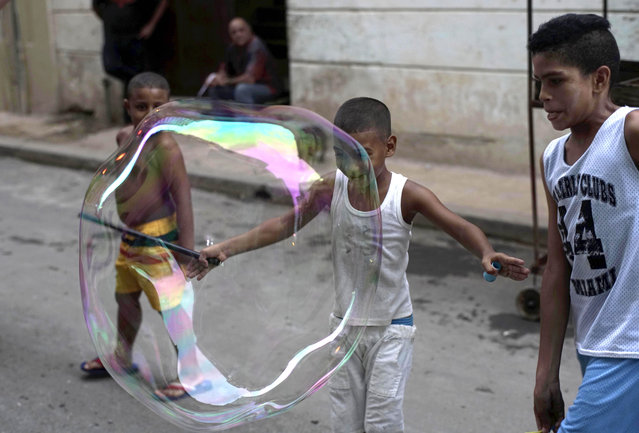 Children play with a giant soap bubble in the streets of Old Havana, Cuba, Wednesday, September 16, 2015. (Photo by Ramon Espinosa/AP Photo)