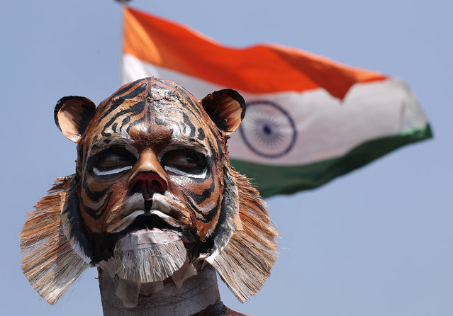 """An Indian activist the """"People for the ethical Treatment of Animals"""" (PETA) Body-painted as a tiger during a protest, on the eve of International Day of Forests in New Delhi, India, 20 March 2018. According to a press release, on the eve of International Day of Forests, Indian activists of PETA Body-painted as a tiger, a zebra, and a giraffe as they protested to urge people not to eat meat as eating meat contributes to species extinction. (Photo by Rajat Gupta/EPA/EFE)"""