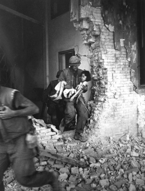 A Marine carries a seriously wounded child from the ruins of a house in Hue, Vietnam, February 6, 1968. (Photo by AP Photo)
