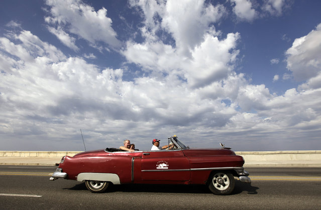 Tourists ride in a Cadillac 1952 convertible along Havana's seafront boulevard El Malecon, February 9, 2010. (Photo by Desmond Boylan/Reuters)