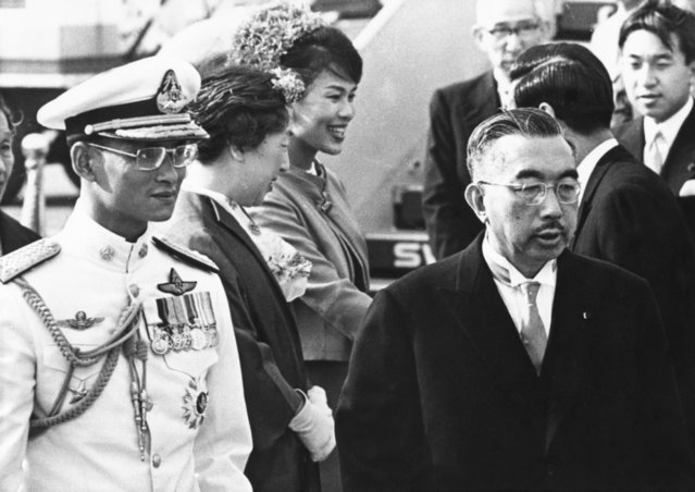 In this May 27, 1963, file photo, Japan's Emperor Hirohito, right, walks with Thailand's King Bhumibol Adulyadej, as he arrives in Tokyo. At rear are Thailand's Queen Sirikit, third from left, and Japan Empress Nagako, second left. (Photo by AP Photo)