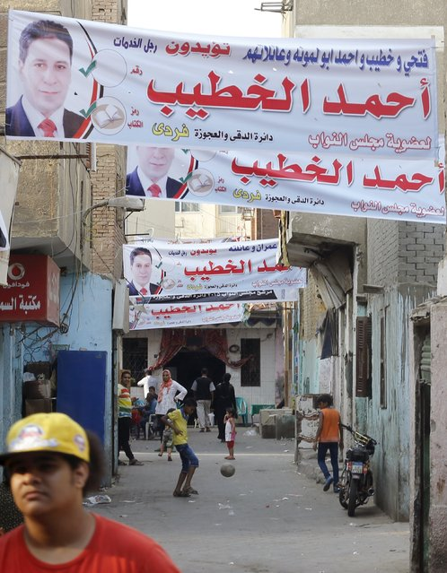 People are seen under election banners of parliamentary candidate Ahmed al-Khatib in Dokki district of Giza governorate, Egypt, September 30, 2015. (Photo by Amr Abdallah Dalsh/Reuters)