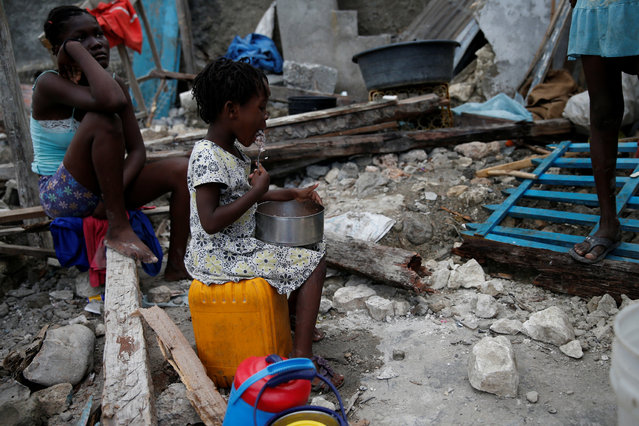 A girl eats at her destroyed house after Hurricane Matthew hit Jeremie, Haiti, October 15, 2016. (Photo by Carlos Garcia Rawlins/Reuters)