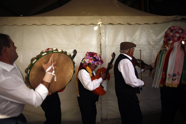 People in traditional costumes play their instruments as they walk on stage before competing in the 53rd Verdiales music contest in Malaga, southern Spain December 28, 2014. (Photo by Jon Nazca/Reuters)