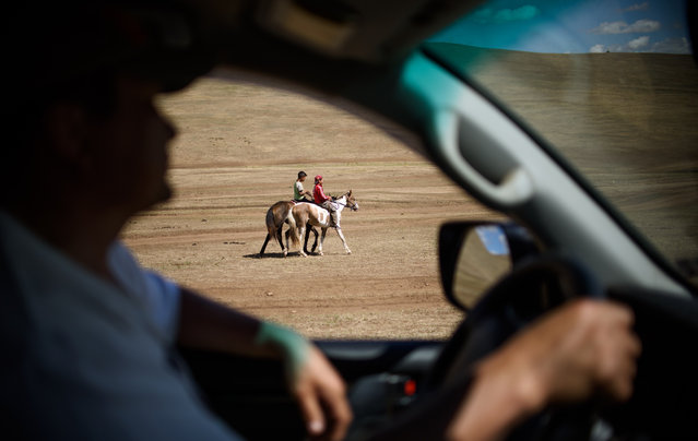 This picture taken on July 8, 2015 shows 13-year-old jockey Purevsurengiin Togtokhsuren (R) riding his horse with a friend while his coach watches from a car during his training session in Khui Doloon Khudag, some 50 kms west of Ulan Bator. (Photo by Johannes Eisele/AFP Photo)