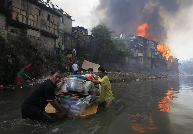 Residents salvage their belongings after a raging fire engulfed around 2,000 houses in Quezon city, metro Manila January 1, 2015. At least eight people, including a seven year-old child, died and thousands were displaced after a fire broke out in different locations in metro Manila as the New Year kicked off, local media reported. (Photo by Romeo Ranoco/Reuters)