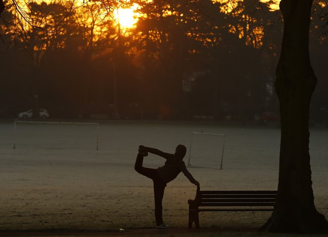 A woman exercises as the sun rises over Victoria Park in Leicester, central England, December 30, 2014. (Photo by Darren Staples/Reuters)