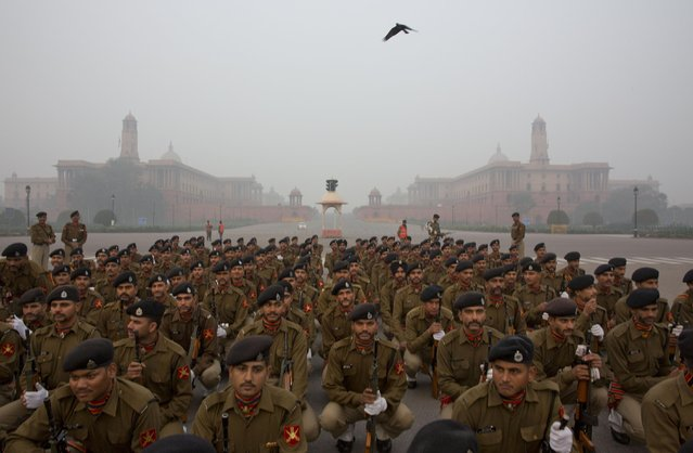Indian paramilitary force soldiers listen to their marching commander before they begin rehearsals for the upcoming Republic Day parade amidst the morning fog, in New Delhi, India, Wednesday, January 7, 2015. Republic Day will be celebrated on Jan. 26. In the background is the Rashtrapati Bhawan, or Presidential Palace. (Photo by Manish Swarup/AP Photo)