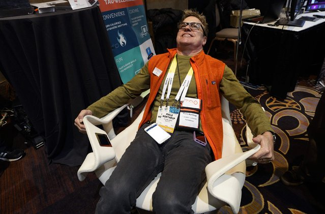 Philo Northrup, president of Tao Wellness, demonstrates the Tao Chair at the International Consumer Electronics show (CES) in Las Vegas, Nevada January 4, 2015. The chair allows a person to get an isometric workout using resistance against the chair while watching TV. (Photo by Rick Wilking/Reuters)