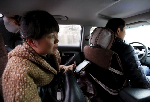 Yoko Wu instructs an Uber taxi driver en route to her office in Beijing, China, November 18, 2015. (Photo by Kim Kyung-Hoon/Reuters)