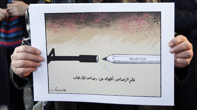 """Caricaturist Stavro Jabra holds up his cartoon during a rally held in solidarity with the victims of a shooting by gunmen at the Paris offices of the satirical weekly newspaper Charlie Hebdo earlier this week, in Beirut January 11, 2015. The words on the cartoon read, """"Pencil lead is stronger than terrorism"""". (Photo by Jamal Saidi/Reuters)"""