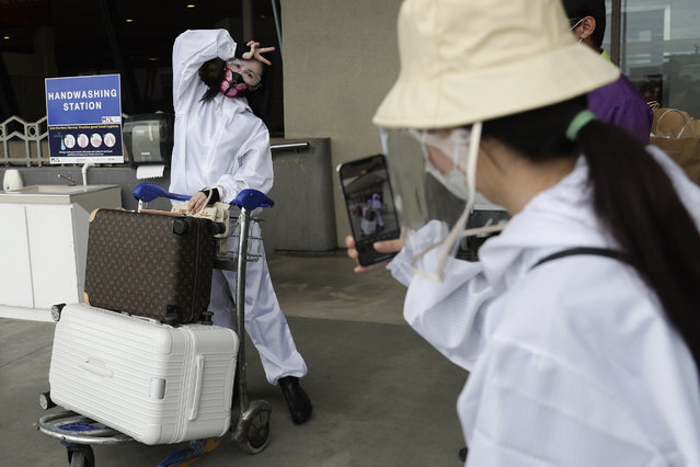 A foreign passenger wearing a protective suit poses as they prepare for their flight at Manila's International Airport, Philippines, Monday, January 18, 2021. (Photo by Aaron Favila/AP Photo)