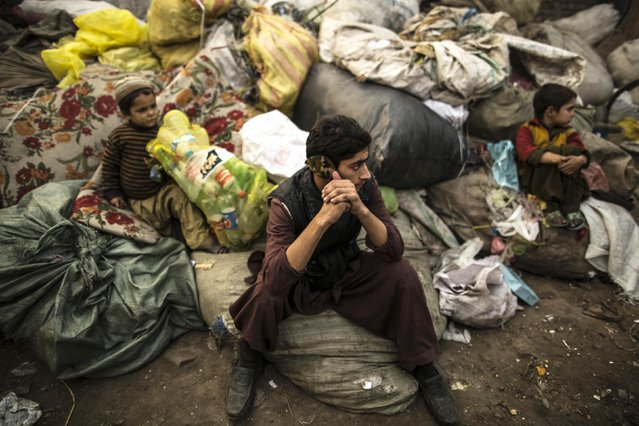 Afghan refugees sit on sacks filled with used plastic items to sell at their makeshift shelter in a slum on the outskirt of Lahore January 12, 2015. (Photo by Zohra Bensemra/Reuters)