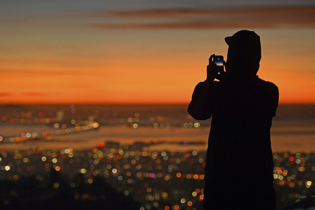 A person stops to take a picture of the sun setting behind the San Francisco skyline as seen from Grizzly Peak Boulevard in Oakland, Calif., Thursday, Dec. 31, 2020. (Photo by Jose Carlos Fajardo/Bay Area News Group via AP Photo)