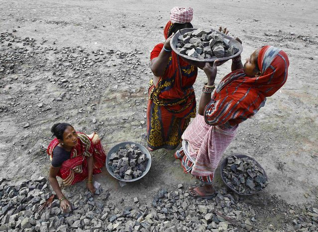 Women labourers work at the construction site of a road in Kolkata January 8, 2015. Across towns and cities in India, it is not uncommon to see women cleaning building sites, carrying bricks and or shoveling gravel - helping construct the infrastructure necessary for the country's economic and social development. (Photo by Rupak De Chowdhuri/Reuters)