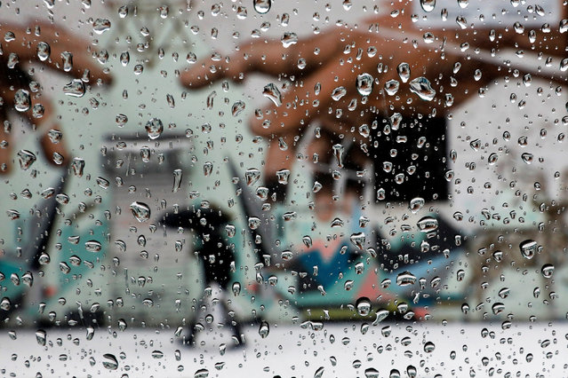 A man with an umbrella is seen through rain drops on a car window walking by a mural in Brooklyn, New York, U.S., February 7, 2018. (Photo by Shannon Stapleton/Reuters)