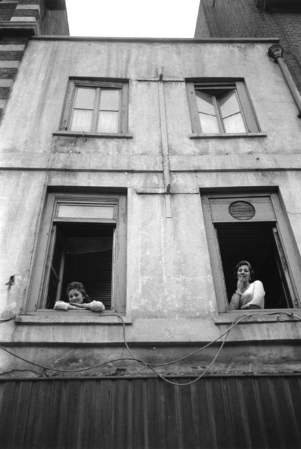 Two prostitutes lean out of the windows of a brothel in Soho, London.  Original Publication: Picture Post - 8593 -  I Am The Queen Of Soho - pub. 1956   (Photo by Thurston Hopkins/Getty Images)