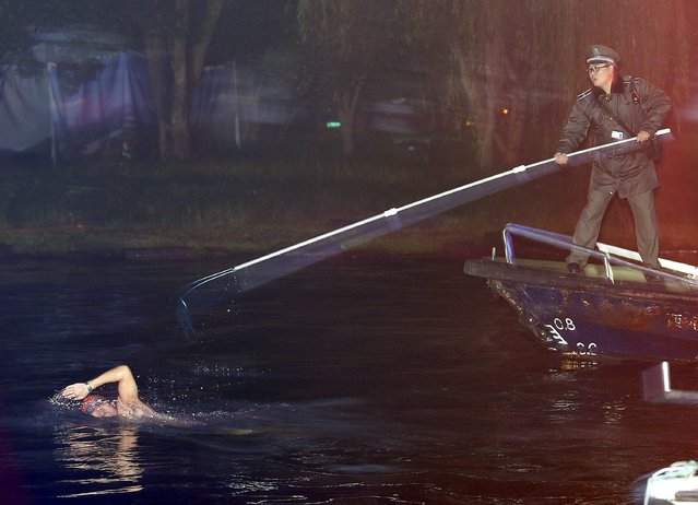 A security personnel (R) tries to stop a man from swimming away after being caught swimming in the West Lake, which is a violation of the resort's regulations, in Hangzhou, Zhejiang province, China, December 1, 2015. (Photo by Reuters/Stringer)
