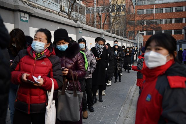 People line up to be tested for the Covid-19 coronavirus in Beijing on January 22, 2021, part of a drive to test two million people in 48 hours as the city rushes to snuff out a new local cluster of cases believed to be linked to a more contagious virus variant. (Photo by Greg Baker/AFP Photo)