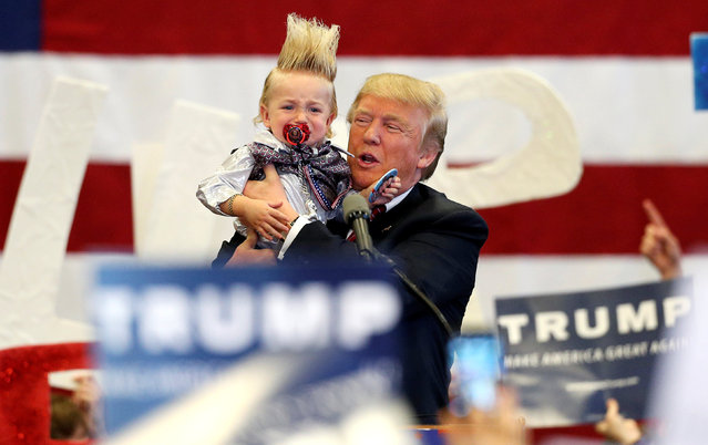 Republican U.S. presidential candidate Donald Trump holds up a crying young child from the crowd as he arrives at a Trump campaign rally in New Orleans, Louisiana March 4, 2016. (Photo by Layne Murdoch Jr./Reuters)
