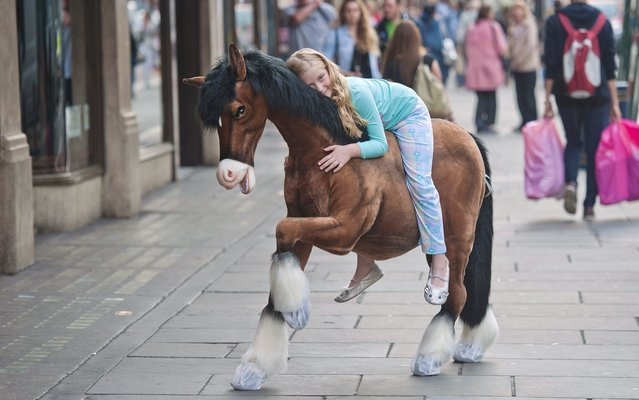 """A child poses for photographs on a Clydesdale Prancing Pony during a photocall at Hamleys toy shop in London on June 27, 2013. Hamleys unveiled  the """"must have"""" toys for Christmas 2013 at the companys' flagship Regent Street store in London. (Photo by Will Oliver/AFP Photo)"""