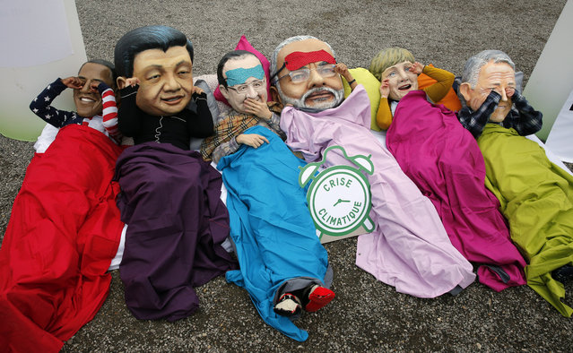 Oxfam activists wear masks of from left, U.S. President Barack Obama, Chinese President Xi Jinping,  French President Francois Hollande, India's Prime Minister Narendra Modi, German Chancellor Angela Merkel and Australia's Prime Minister Malcolm Turnbull as they stage a protest during the COP21, United Nations Climate Change Conference in Le Bourget, north of Paris, Thursday, December 10, 2015. (Photo by Christophe Ena/AP Photo)