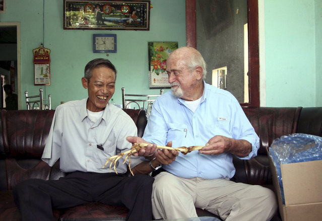 Dr. Sam Axelrad, right, hands over arm bones belonging to former North Vietnamese soldier Nguyen Quang Hung, left, at Hung's house in the town of An Khe, Gia Lai province, Vietnam on Monday July 1, 2013. In October 1966 Axelrad amputated Hung's arm after the soldier was shot in the arm in an ambush by American troops in the coastal province of Binh Dinh in the former South Vietnam. After decades of silence, the two veterans resumed contact after a Vietnamese journalist wrote an article in a newspaper last year about Axelrad's search for Hung, prompting Hung's brother in law to contact the newspaper's editors. (Photo by Kha Hoa/AP Photo/Thanh Nien Newspaper)