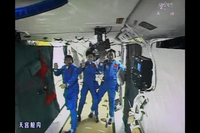 A photo of the giant screen at the Jiuquan space center shows Chinese astronauts (from left) Liu Wang, Jing Haipeng and Liu Yang in the Tiangong-1 module on June 18, 2012. The three astronauts entered an orbiting module for the first time, in a move broadcast live on China's state television. (Photo by STR/AFP Photo via The Atlantic)