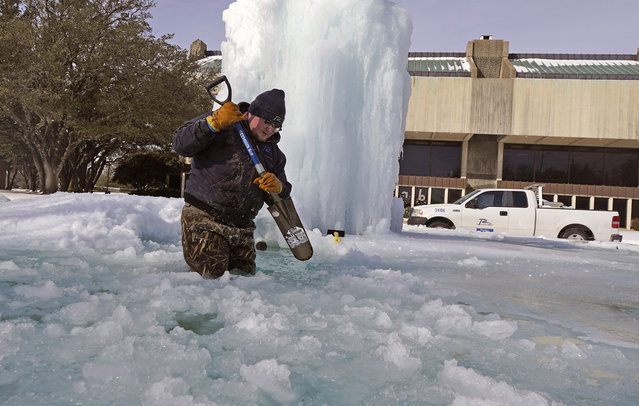 City of Richardson worker Kaleb Love breaks ice on a frozen fountain Tuesday, February 16, 2021, in Richardson, Texas. Temperatures dropped into the single digits as snow shut down air travel and grocery stores. (Photo by L.M. Otero/AP Photo)