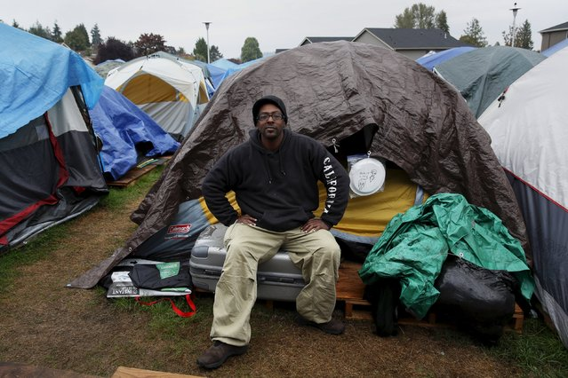 "Aaron Ervin, 50, poses in front of his tent at SHARE/WHEEL Tent City 3 outside Seattle, Washington October 8, 2015. ""Tent City has been a saving grace for me, a place for me to refresh and gather my thoughts. While I'm here I want to lead by example and be (a) positive influence on camp. People feel safe here, they are tense from being wrongfully judged from carrying all their bags as being homeless and the camp makes you feel comfortable knowing you have a safe place for your belongings, which does a lot for people making them more relaxed"". (Photo by Shannon Stapleton/Reuters)"