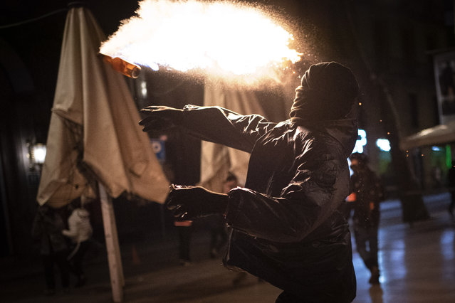 A protestor throws a molotov cocktail at police during clashes following a protest condemning the arrest of rap singer Pablo Hasél in Barcelona, Spain, Saturday, February 27, 2021. After a few days of calm, protests have again turned violent in Barcelona as supporters for a jailed Spanish rapper went back to the streets. (Photo by Emilio Morenatti/AP Photo)