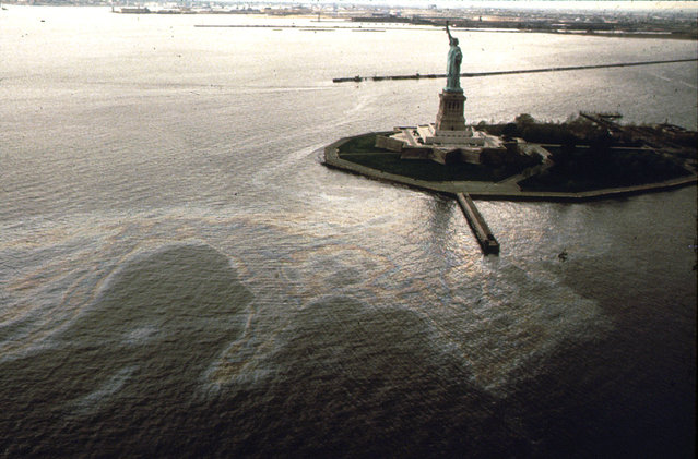 An oil slick surrounds Liberty Island in New York Harbor, in May of 1973. (Photo by Chester Higgins/NARA via The Atlantic)