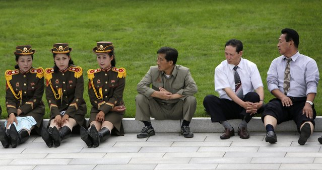 North Korean men look at members of a military band as they wait for the opening ceremony of the Victorious Fatherland Liberation War Museum, in Pyongyang July 27, 2013. North Korea is celebrating the 60th anniversary of the signing of a truce in the 1950–1953 Korean War. (Photo by Jason Lee/Reuters)