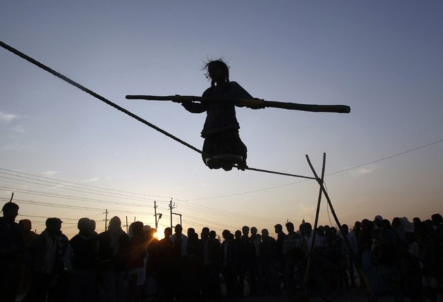 Tightrope walker Siba, 9, is silhouetted against the setting sun as she holds a balancing pole while performing on a rope, on the banks of river Ganga in the northern Indian city of Allahabad January 30, 2015. (Photo by Jitendra Prakash/Reuters)